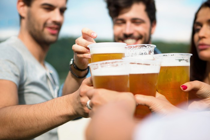 A group of friends toast each other with a beer.