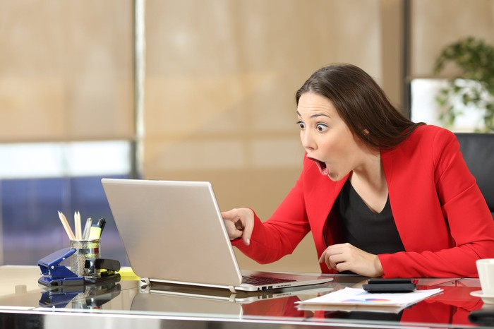 Excited professional woman in a red dress, pointing at her laptop screen in amazement.