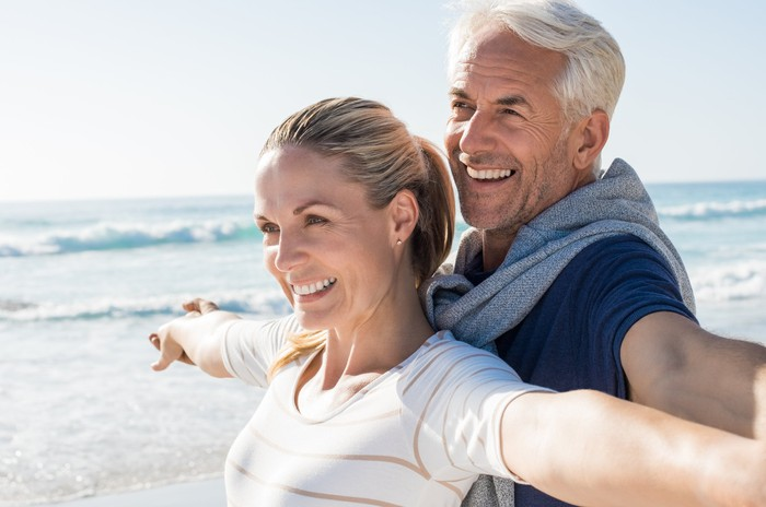 Older couple smiling, standing on a beach.
