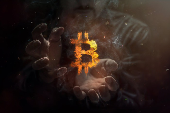 Burning symbol of bitcoin with a person's hands in the background.