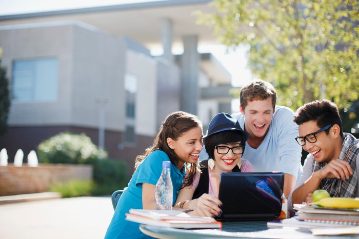 College-age people smiling and all looking at a single laptop screen on a sunny day.
