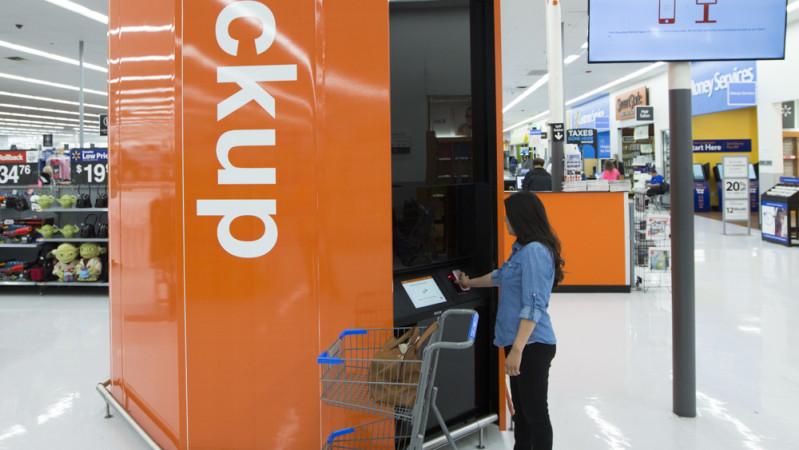 A customer entering information into a pickup tower at Wal-Mart.