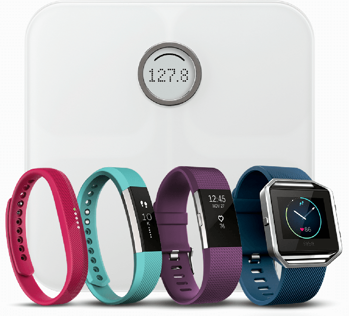 Five of Fitbits devices, a smart scale and four wristband worn activity trackers.