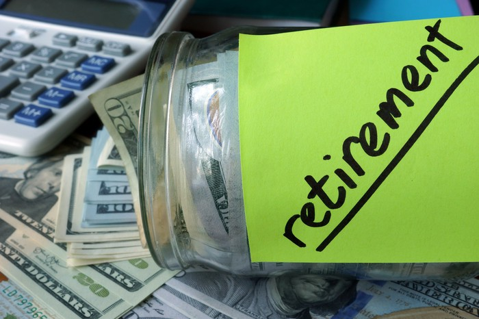 Jar holding cash with a green Post-It with the word retirement on it, on a desk with a calculator and more cash.