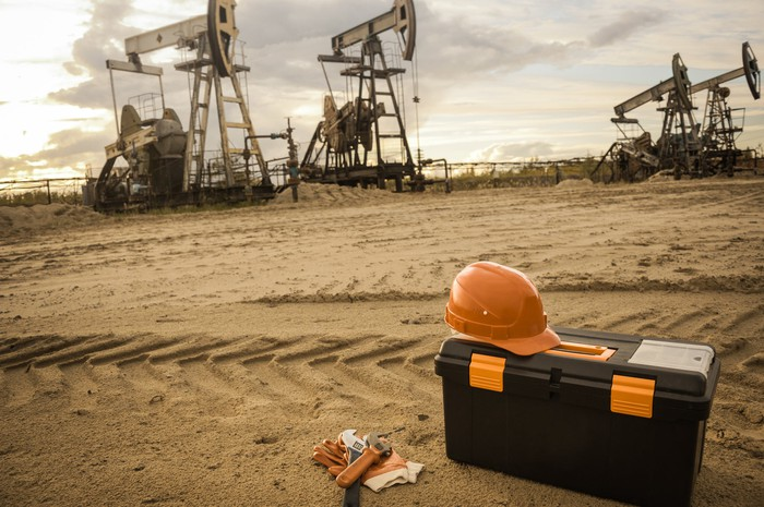 A tool box near some oil pumps.