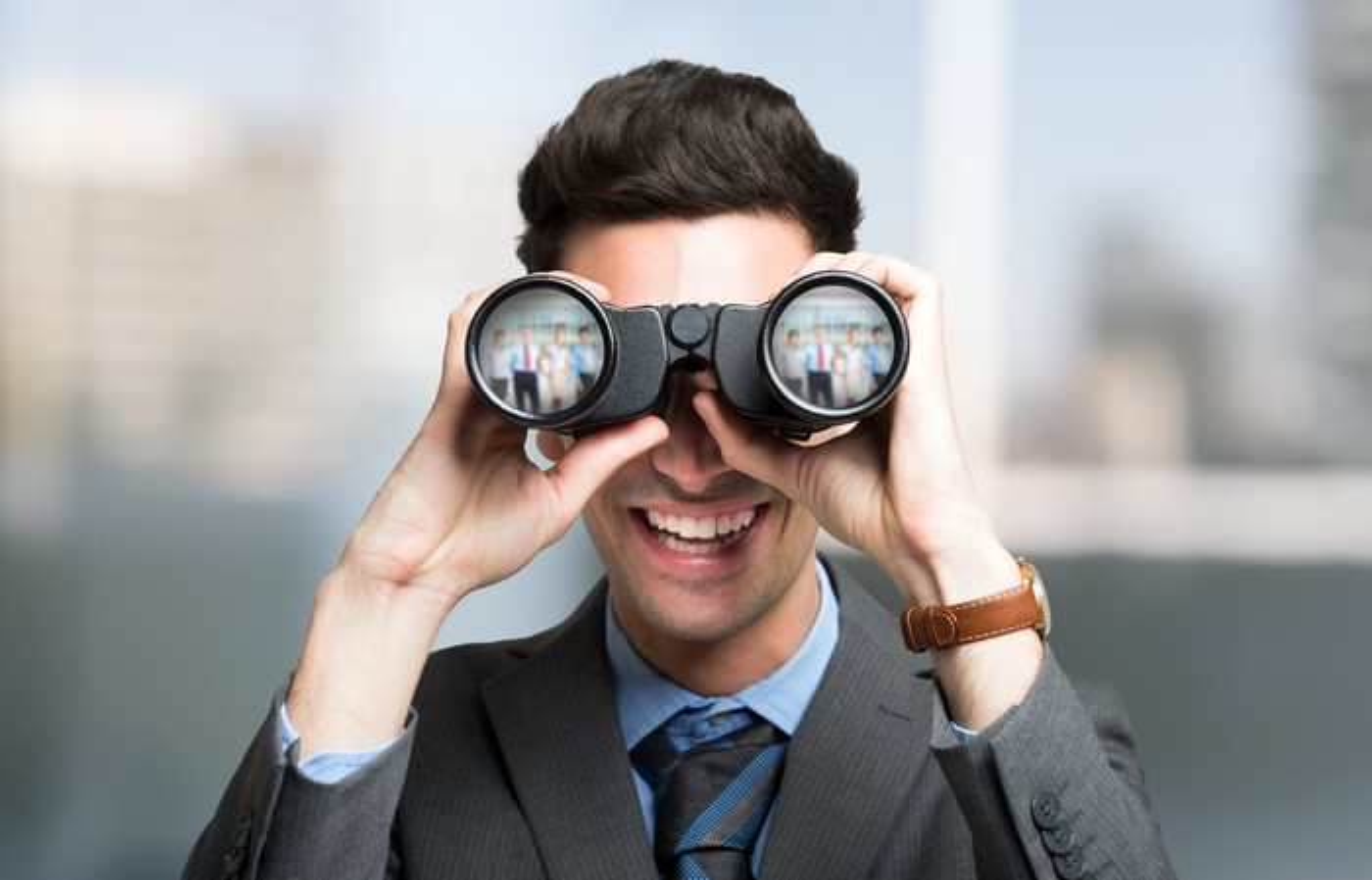Businessman looking into binoculars.