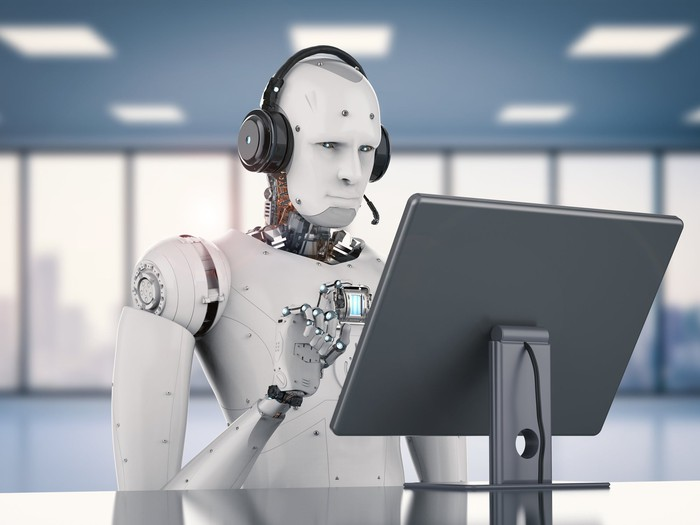 Robot with headphones types on a computer.