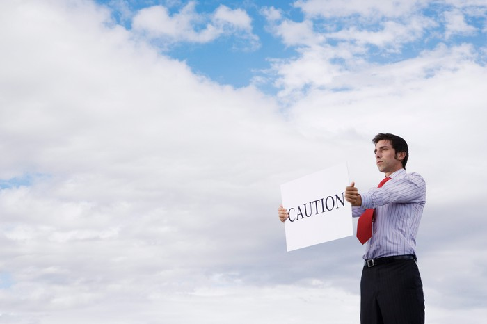 Business man holding a sign that says caution.