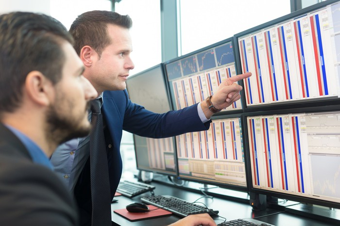 Two businessman looking at financial charts on an array of computer monitors.