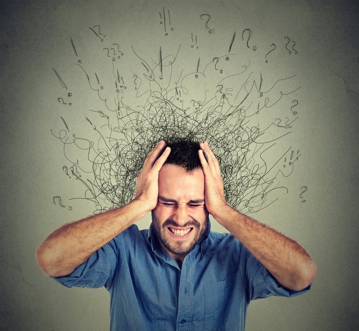 Stressed man upset frustrated has too many thoughts with brain melting into lines question marks.
