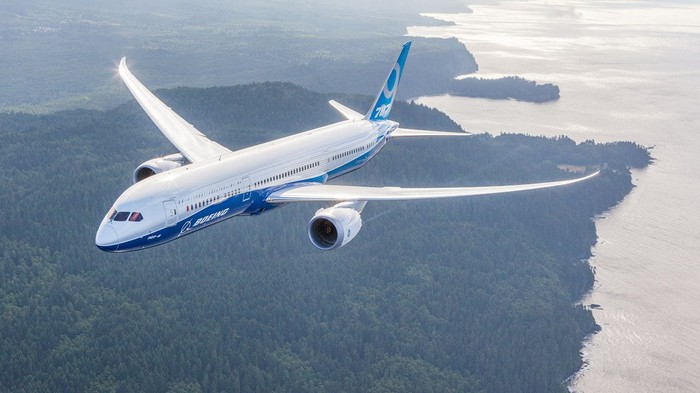 Boeing white and blue 787 Dreamliner aircraft, airborne over a wooded coastline on a large body of water.