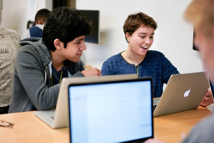 Students in a classroom smiling looking at Apple laptops.