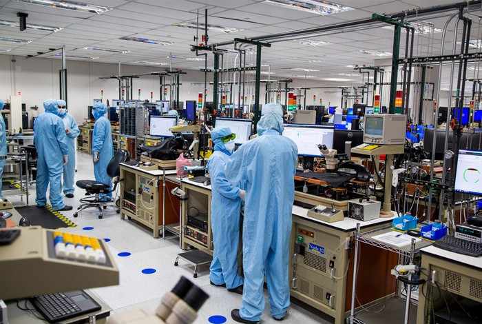 Workers in a factory clean room, wearing surgical-type scrubs.