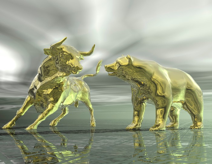 Two gold statues of a bull and a bear face off against a cloudy, grey backdrop.