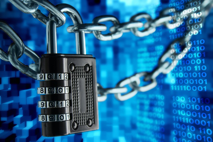 A chain link with a padlock on it in front of a blue background containing rows of the digits 0 and 1 -- concept for blockchain.