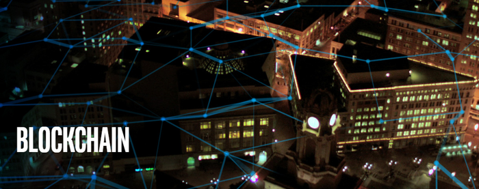 Aerial view of a city at night with blue lines connecting various parts of the image -- concept for blockchain.