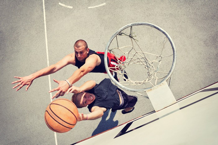 An attempted layup on an outdoor basketball court.