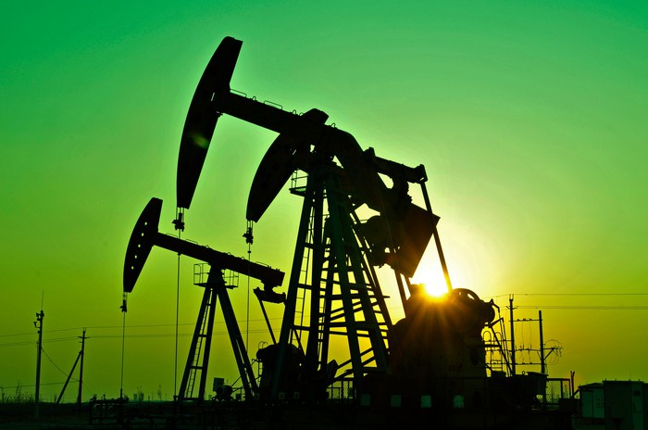 Oil pumpjacks in front of a green sky.