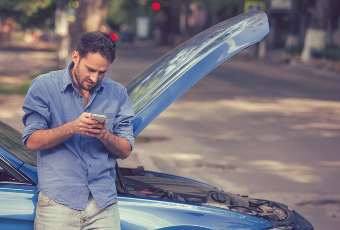 Man looking at his phone while standing next to a car with its hood up