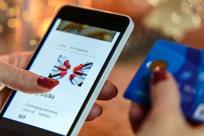 Woman shopping on a smartphone while holding a credit card