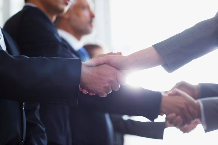 Men in business wear shaking hands