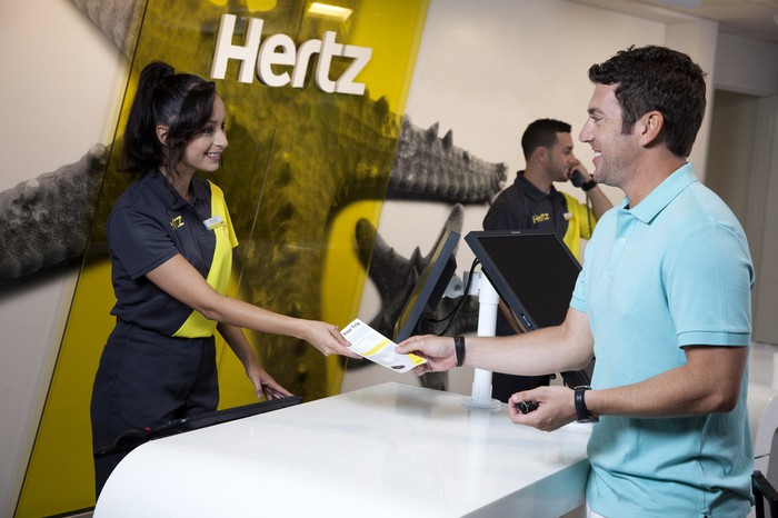 Rental car agent handing document to customer, with Hertz logo in the background.