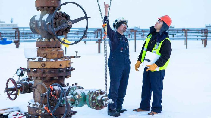 Two workers next to a wellhead having a conversation, on a field covered in ice or snow.
