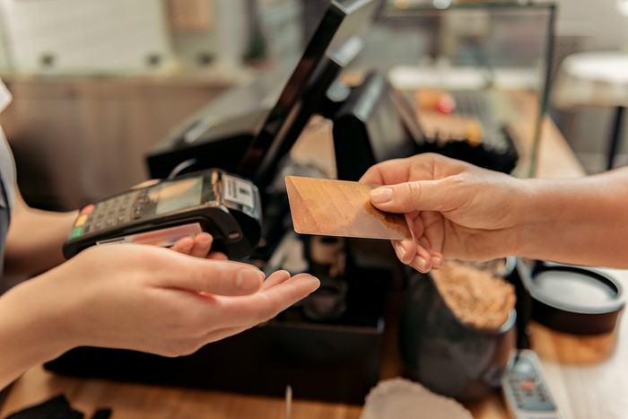 One person handing a card to another at a register