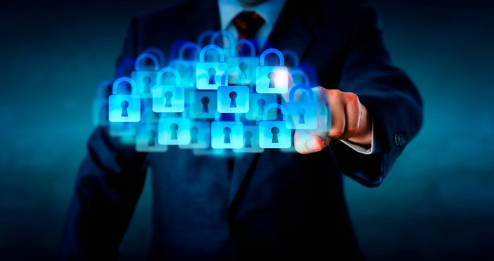 "A businessman presses a ""cloud"" of digital padlocks."