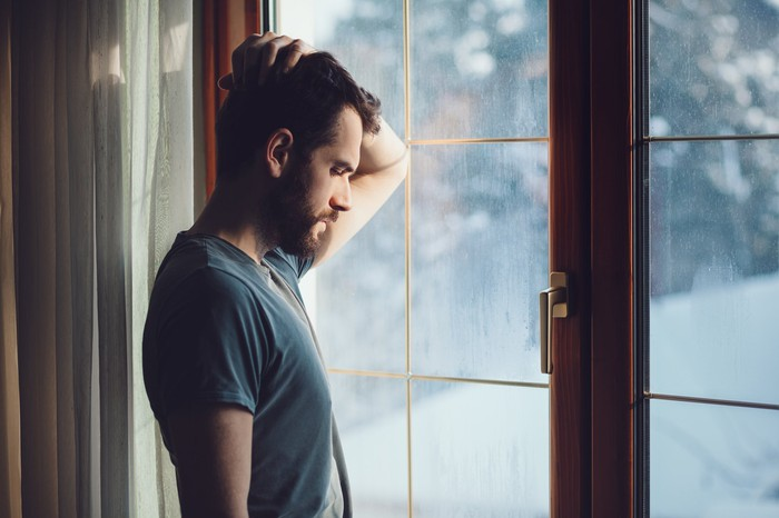 A man stands before a glass door, head on hand, head bowed, and eyes closed.