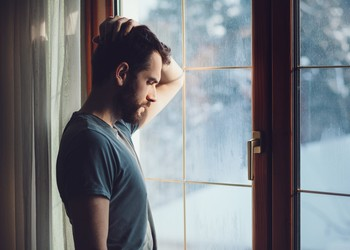 man staring out window_GettyImages-638779972