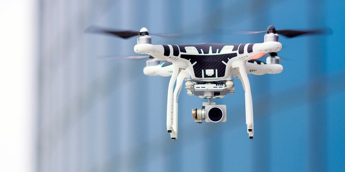A flying drone carrying a camera.