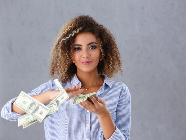 young woman making it rain 100-dollar bills money cash rich POC