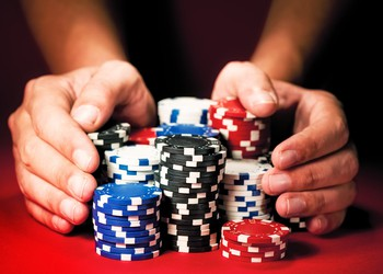 hands sliding stacks of poker chips across table gamble risk bet