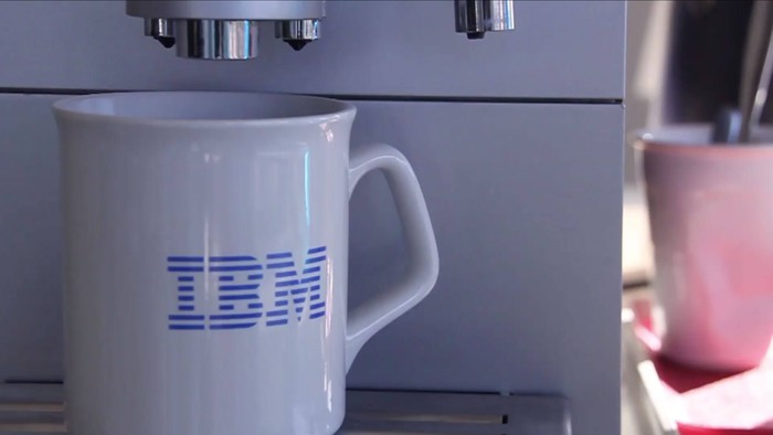 White coffee mug with IBM logo under the spigot of a coffee machine.
