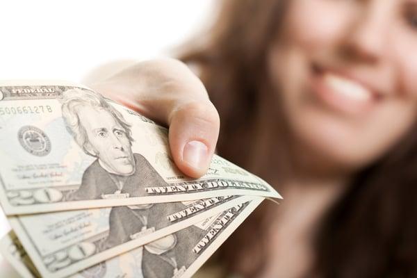 Woman handing over three $20 bills
