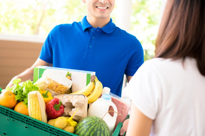A smiling man in a blue shirt carrying a box full of fresh produce and milk and about to hand it to a woman customer