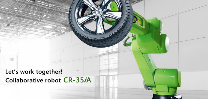 A bright green-colored collaborative robot holding an automobile tire in an empty factory.