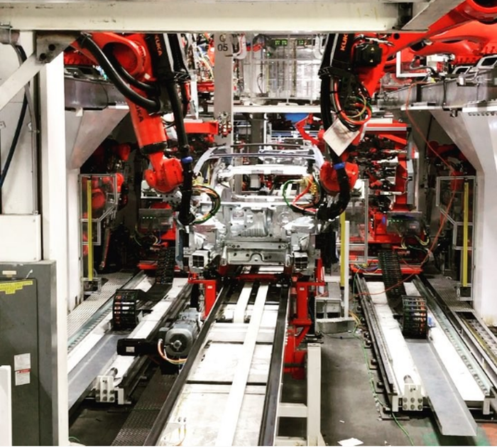Model 3 production line, showing red robotic arms on both sides of an assembly line.