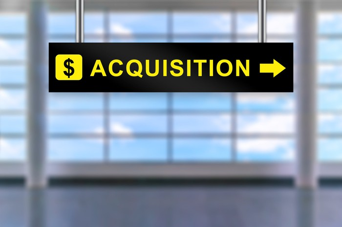 """Airport sign with dollar symbol, the word """"acquisition"""", and an arrow pointing right"""