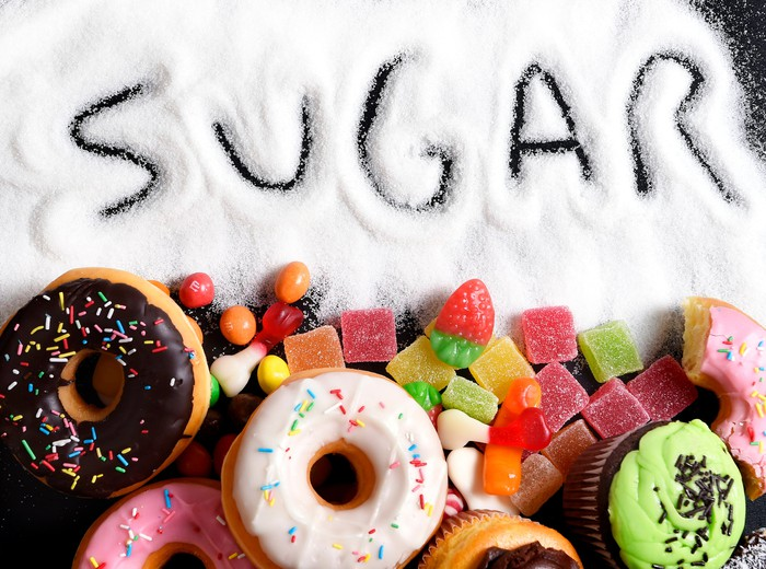 The word sugar drawn out in white sugar, next to donuts and candy.