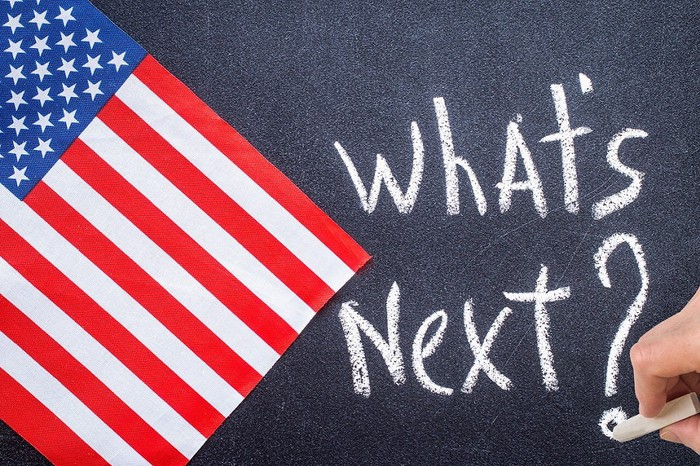 What's Next? written on chalkboard next to an American flag.