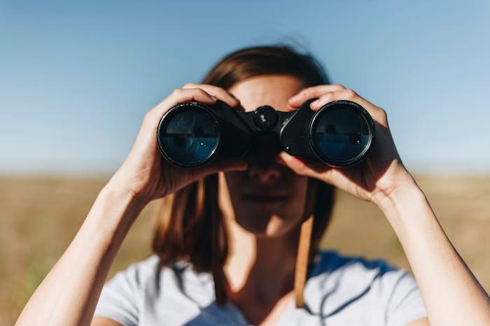 Woman looking through binoculars.