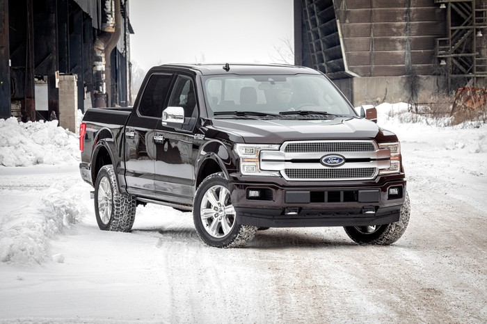 A black 2018 Ford F-150 pickup parked on a snowy road.
