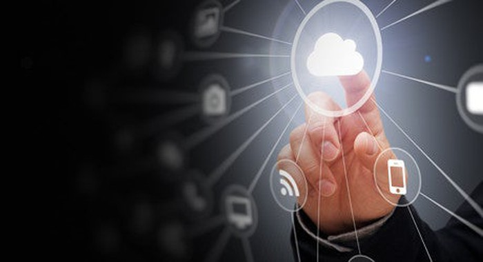 Picture of a hand touching a clear, digital screen with a cloud lit up in the middle connected to multiple data points.