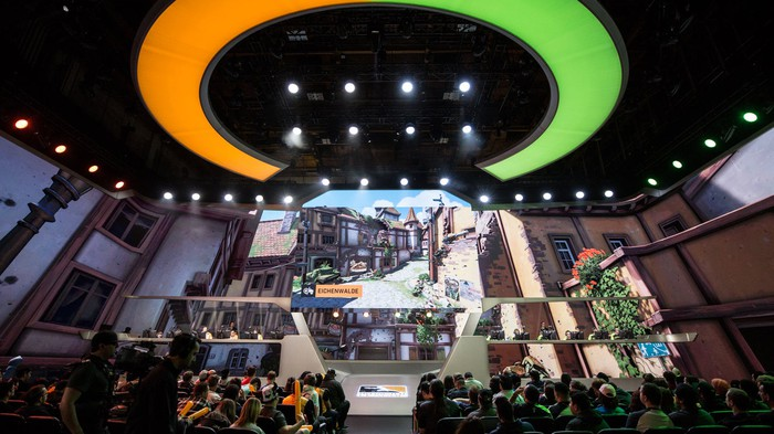 An audience watching players on a stage compete during a regular season match of Overwatch League.
