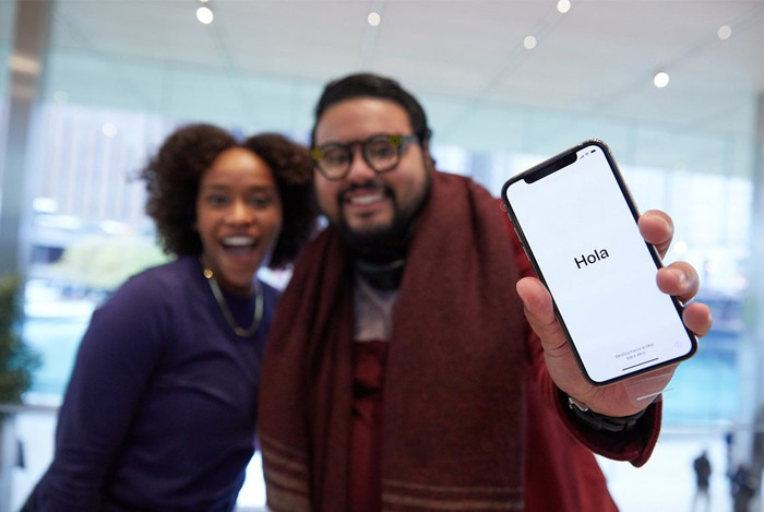Two people, including an Apple customer holding the iPhone X on launch day