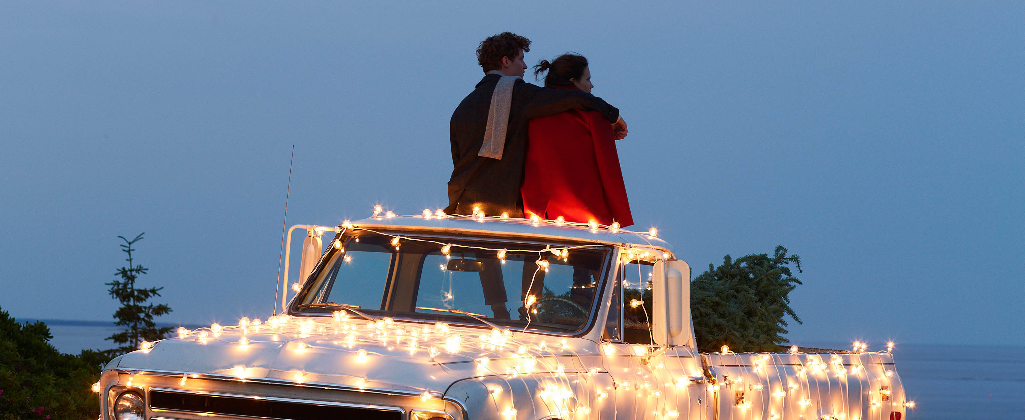 A teen couple sitting on the top of a pickup truck festooned with lights