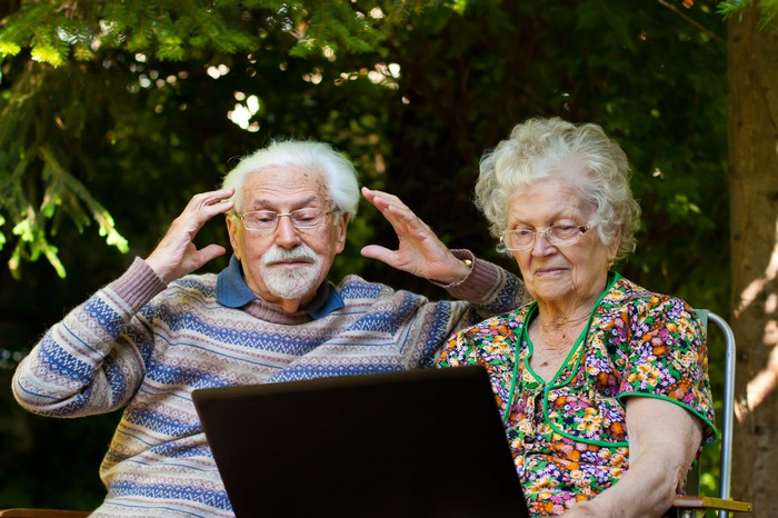 Couple reading news on a laptop