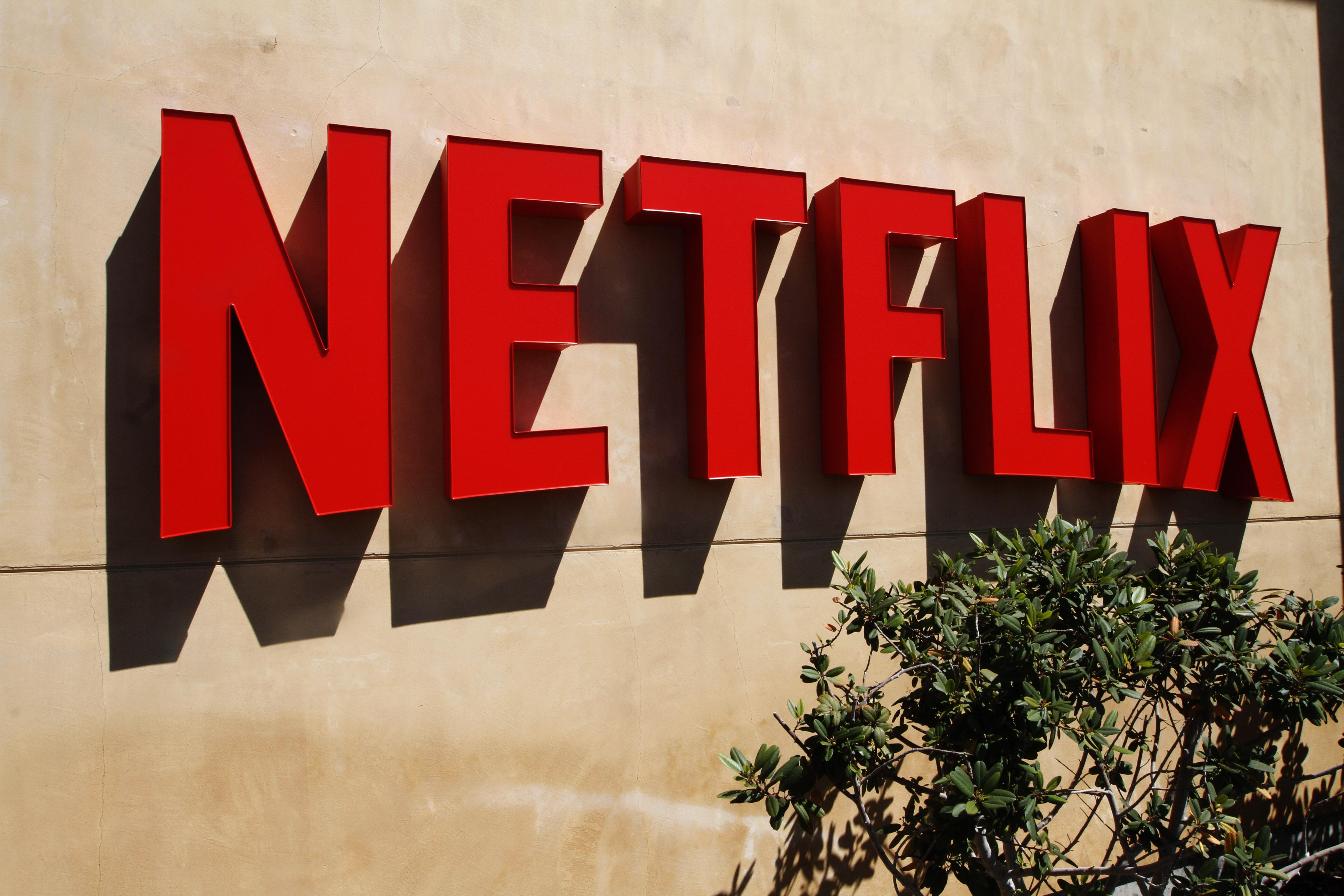 Red Netflix logo on a beige stucco wall outside company headquarters.